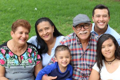 Three generations of a hispanic family in the park, smiling